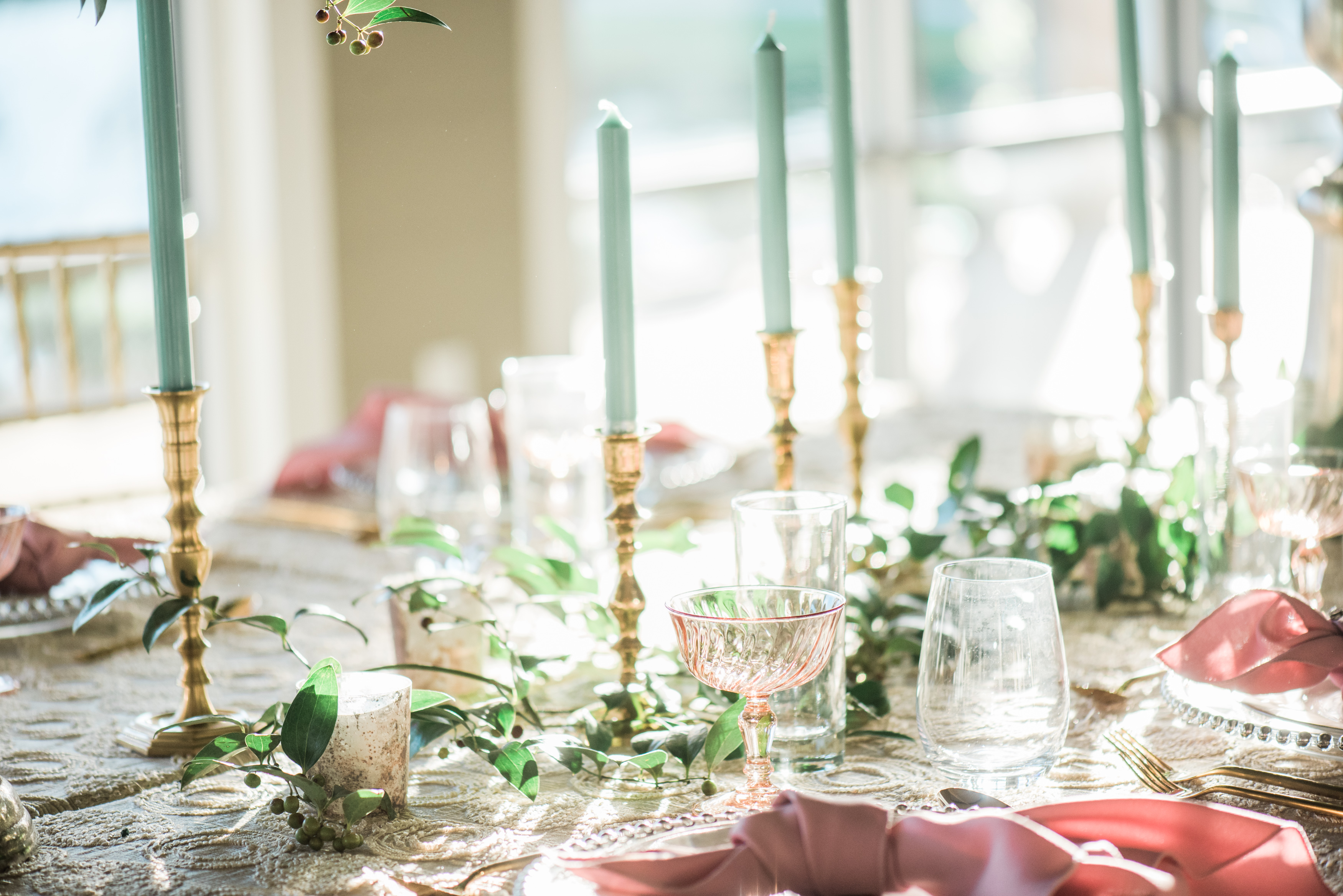 Inn at Quarry Ridge wedding table designed with sea foam green candles in brass candlestick holders and blush linen napkins on clear glass plates with sun streaming through windows in the background by Wedding Photographer in Houston Thomas Ross Photography