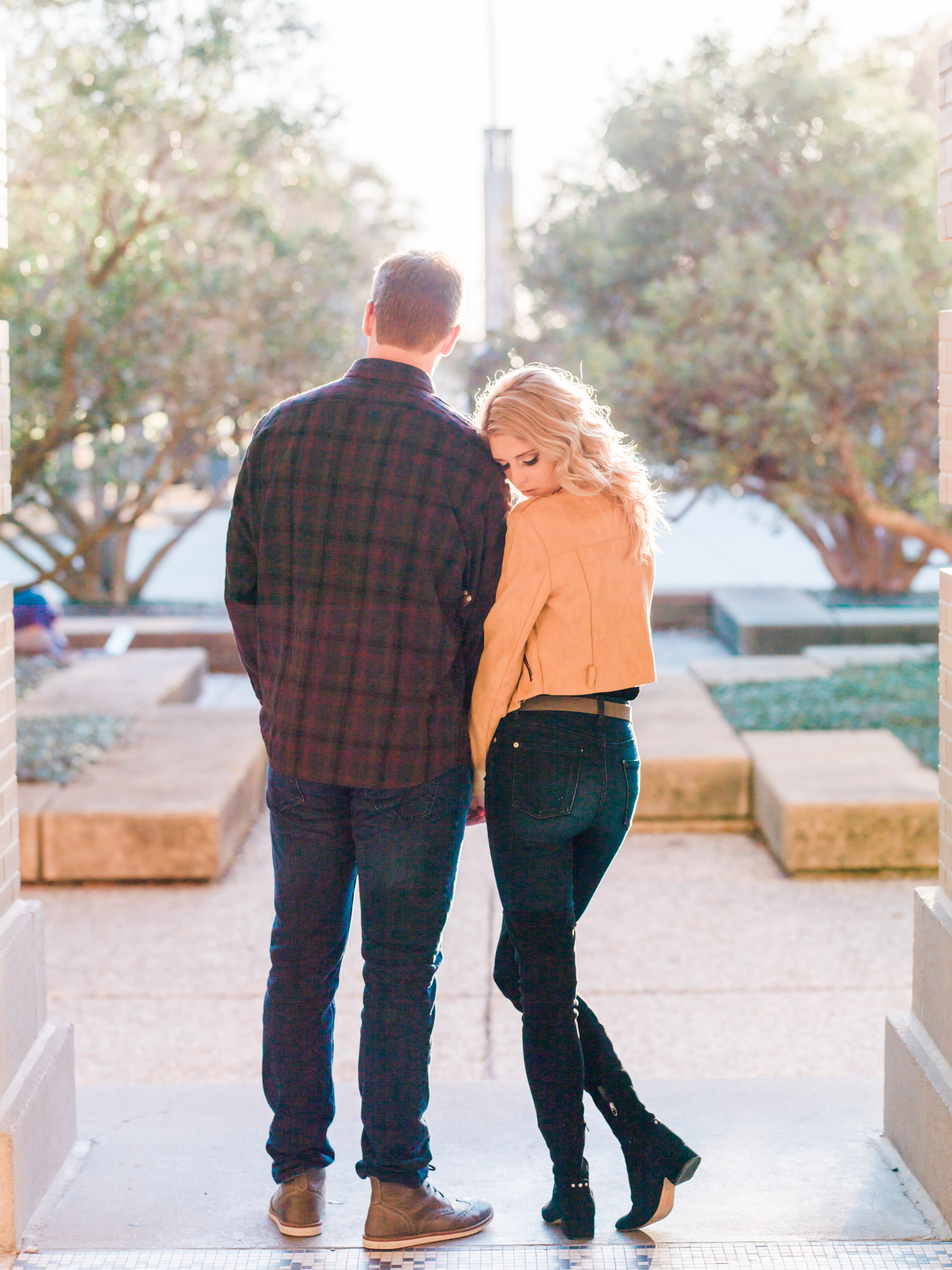 Houston Couple holding hands looking out on Academic Plaza at Texas A&M bride wearing a yellow jacket with blonde hair by Houston Wedding Photographer Thomas Ross Photography